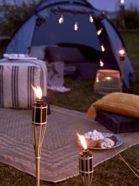 Glamping z niebieskim namiotem, pufem, dywanem zewnętrznym oraz lampkami