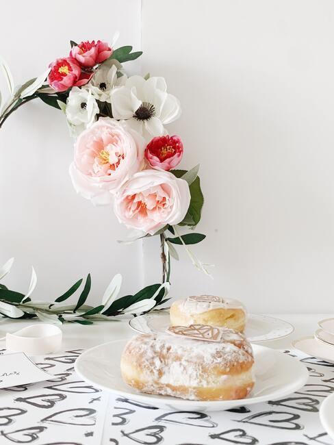 Białe pomieszczenie z wiankiem na ścianie oraz białym talerzem z ciastkami