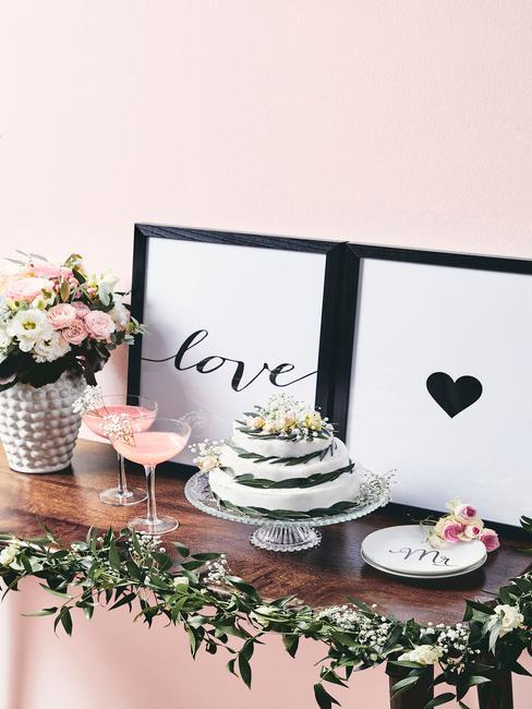 Drewniana półka z wazonem kwiatów, paterą z ciastem, kieliszkami oraz obrazkami