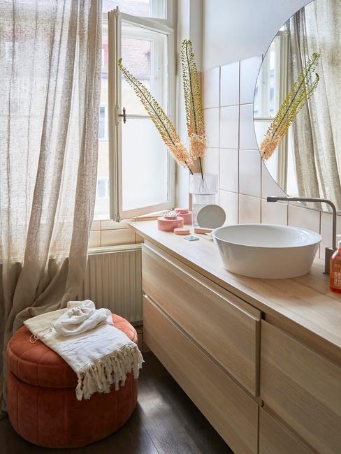 Zbliżenie na drewnianą komodę z pufem, zasłoną, wazonem z kwiatami oraz dodatkami