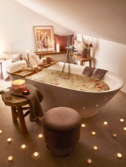 Łazienka na poddaszu z wanną, drewnianym stołkiem, pufem oraz dekoracjami