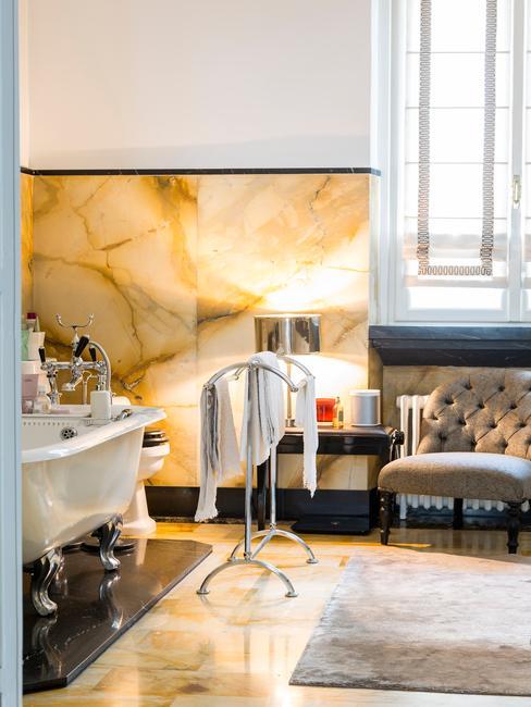 elegancka łazienka z beżowymi płytkami, szarą sofą, wanną i dekoracjami