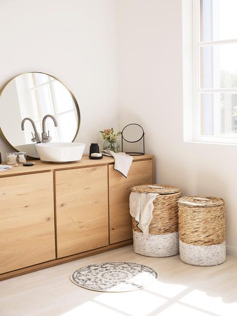 Łazienka w drewnie z drewnianą komodą, lustrem oraz rattanowymi koszami