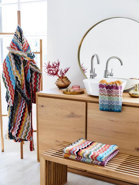 Fragment łazienki w drewnie z komodą, lustrem oraz tekstyliami w stylu boho