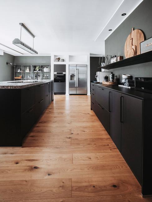 Industrialna kuchnia z ciemną ścianą, czarnymi frontami szafek, drewnianym parkietem oraz dodatkami