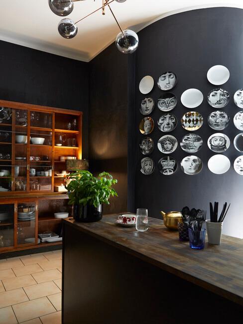 Kuchnia z czarną ścianą, na której znajdują się talerze, drewniana półka oraz wyspa kuchenna
