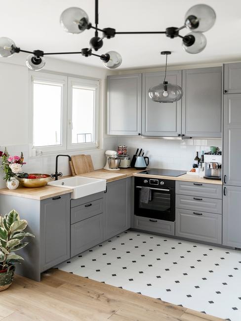 otwarta kuchnia na salon z czarno-białymi płytkami oraz szarymi frontami szafek