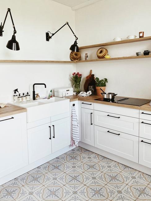 Biała kuchnia w stylu country z drewnianymi szafkami, drewnianymi blatami oraz półkami z akcesoriami kuchennymi