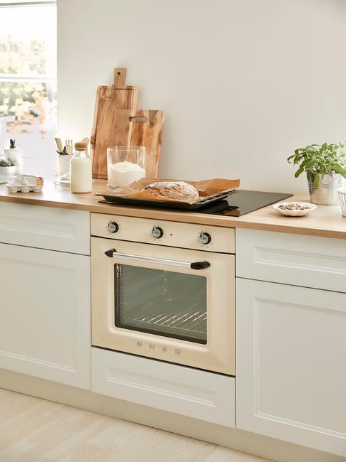 Zbliżenie na beżową kuchankę w białej, minimalistycznej kuchni z białymi frontami szafek oraz dodatkami