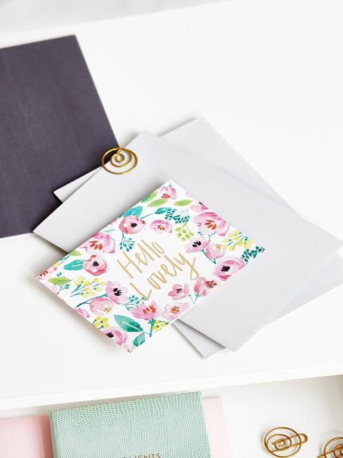 Kolorowa kartka z kopertami na białym biurku