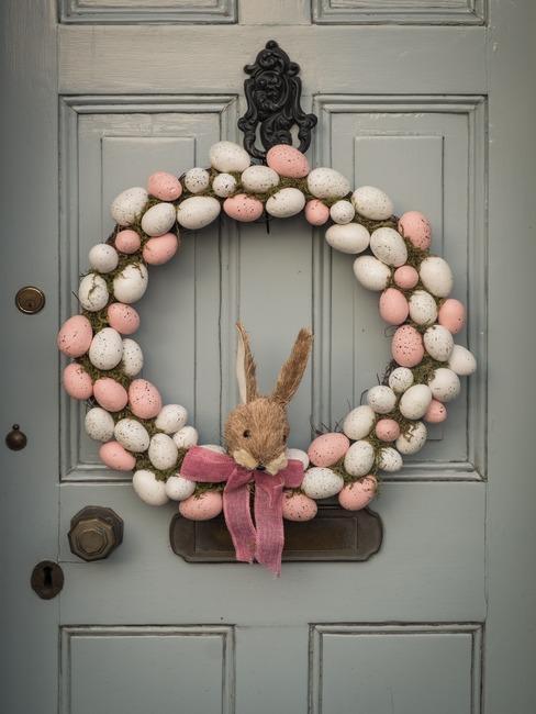 Pastelowy stroik wielkanocny na drzwiach z pisanek oraz zajączkiem