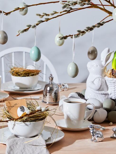 Drewniany stół z białą zastawą, figurką zajączka wielkanocnego oraz kompozycją z gałązkami wierzby
