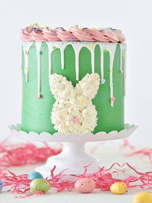 Biała patera z tortem z zielonym lukrem oraz dekoracją z kremu w kształcie zajączka wielkanocnego