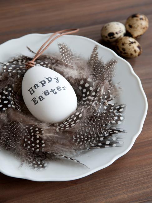 Biały talerz z pisanką oraz piórkami na drewnianym stole
