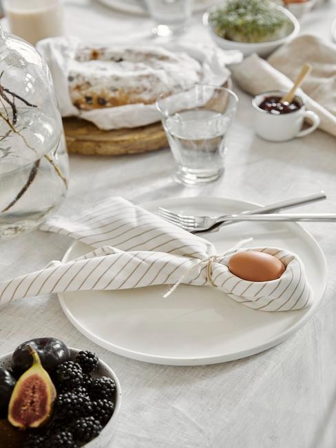 Zbliżenie na biały talerz na stole z serwetką złożoną na kształtów uszów zająca