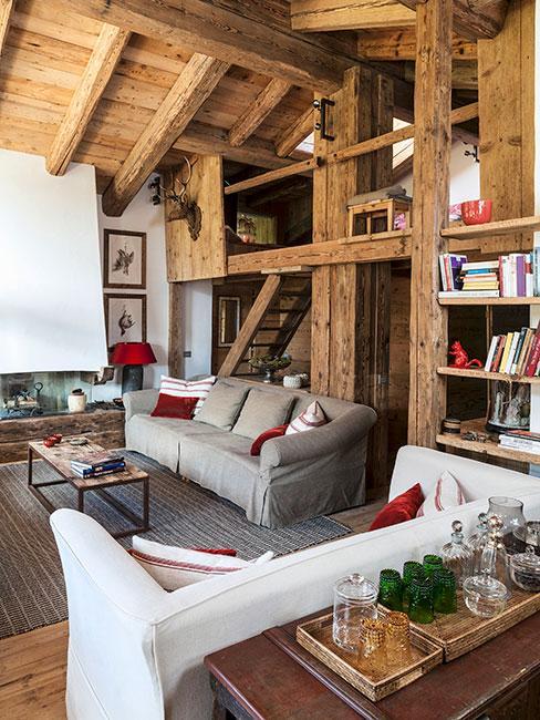 wnętrze drewnianej chaty chalet z szarą sofą