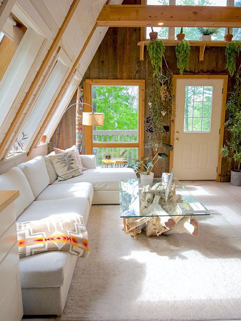 chata górska w stylu skandynawskim z beżową sofą i szklanym stolikiem kawowym opartym na konarze drzewa