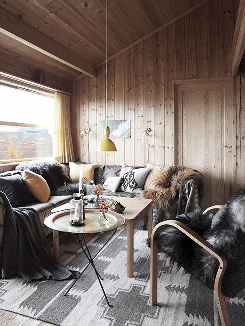 Przytulny salon w chacie górskiej w stylu chalet z szarymi sofami