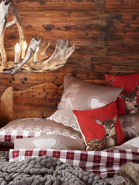 świąteczna pościel z jeleniami na tle drewnianej ściany, z lampą z poroża