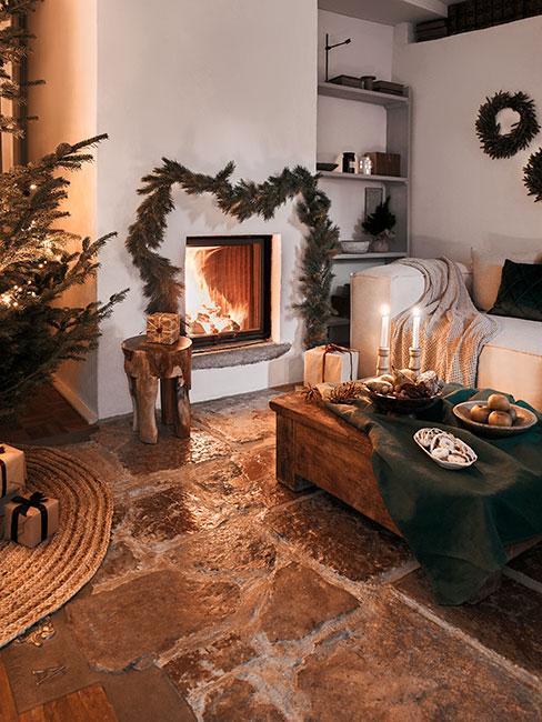 Przytulny salon z kamienna posadzką, białą sofą i kominkiem