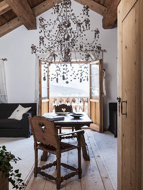 Rustykalna jadalnia z drewnianym stołem i krzesłem i okazałym srebrnym żyrandolem w chatce chalet