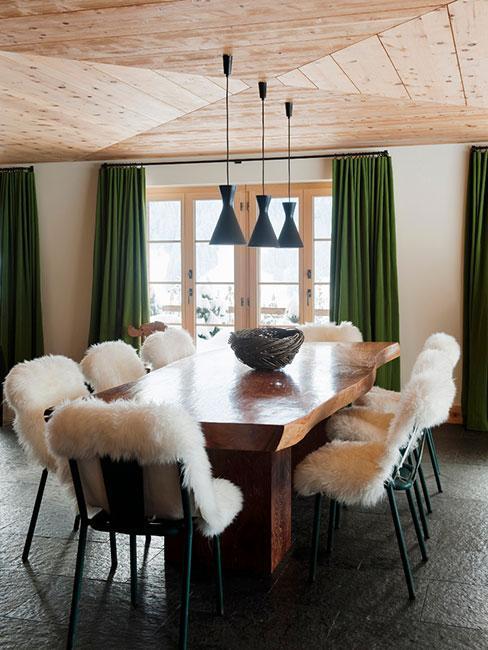 Jadalnia w stylu indistrialnym z owczą skórką na krzesłach w drewnianym domku