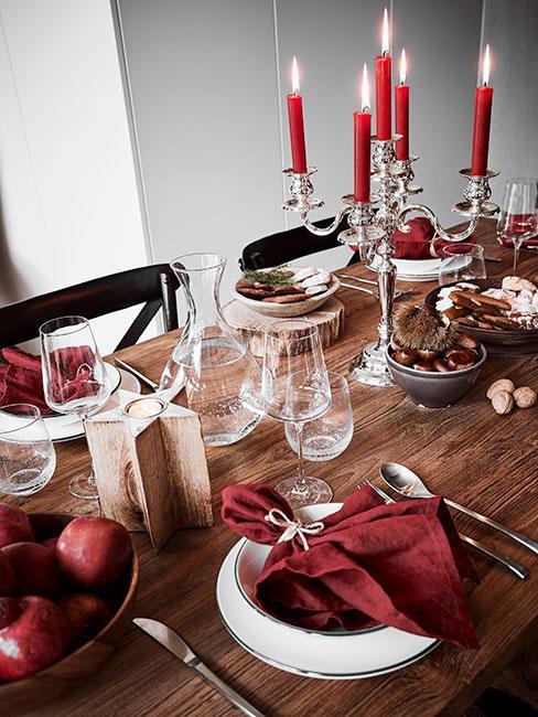 stół do jadalni nakryty białymi naczyniami, przyozdobiony czerwonymi serwetkami i świeczkami