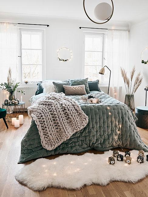Przytulna sypialnia z zieloną narzutą, grubym pledem i owczą skórą na podłodze
