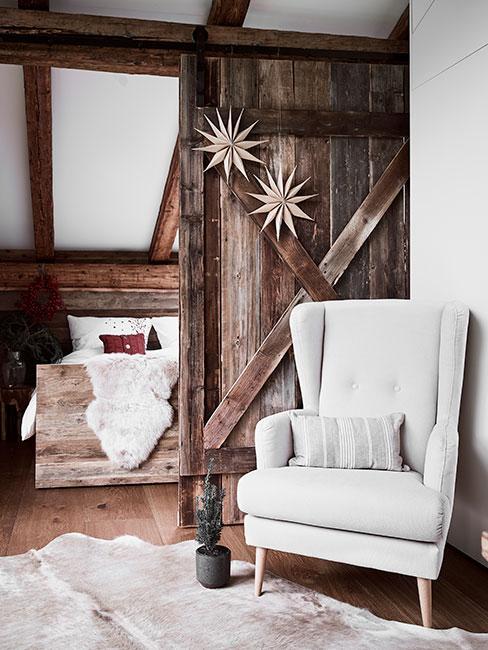 Jasnoszary fotel uszak na tle drewnainej ściany z drewnainą sypialnią w tle w chatce chalet