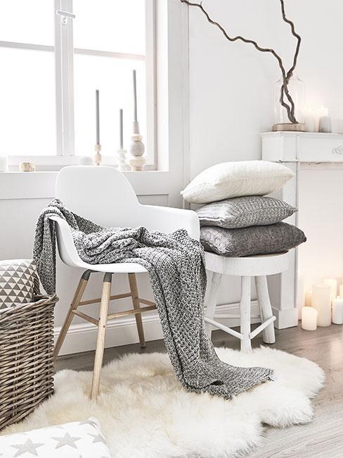 Kącik z białym skandynawskim białym krzesłem i szarym pledem przy białej atrapie kominka