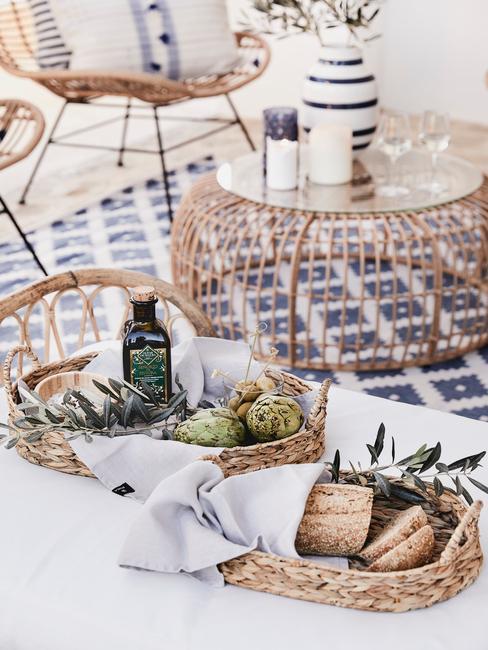 Zbliżenie na rattanowy stolik z wazonem oraz daniami w koszyczkach