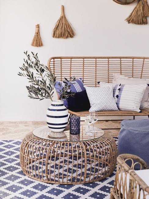Zbliżenie na sofę oraz stolik z rattanu na tarasie wraz z niebieskimi dodatkami