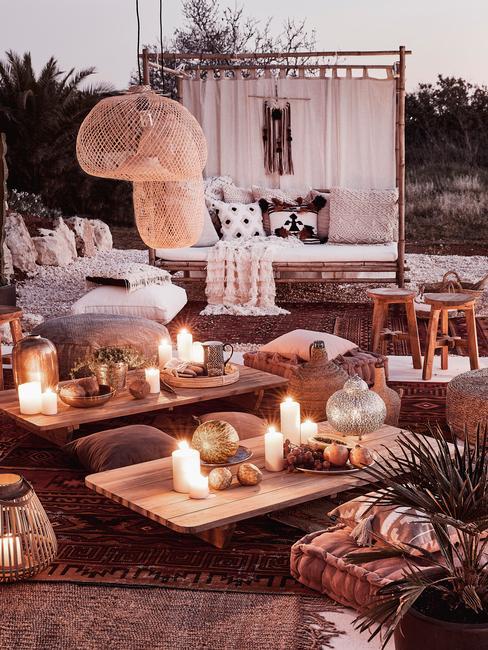 Taras w stylu boho z drewnianymi meblami, dużą ilością świeczek i latarenek oraz dekoracji