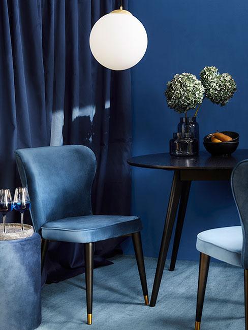 ciemnoniebieska jadalnia z krzesłami z aksamitu, czarnym okrąłym stołem i hortensjami w wazonie