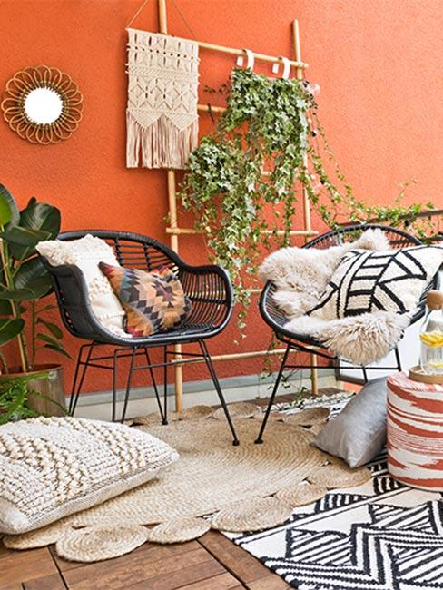 Balkon boho z czarnymi krzesłami z rattanu na tle pomarańczowej ściany