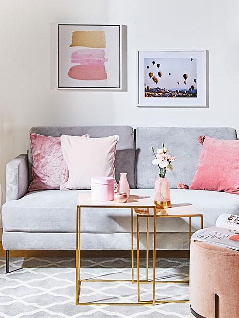szara sofa z aksamitu z różowymi poduszkami i złotymi stolikami pomocniczami w stylu glamour