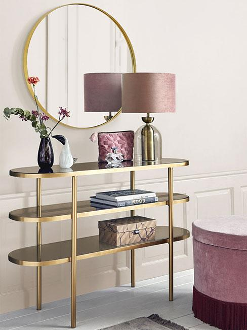 Konsola w złotym kolorze z różową lampą i dekoracjami w stylu glamour