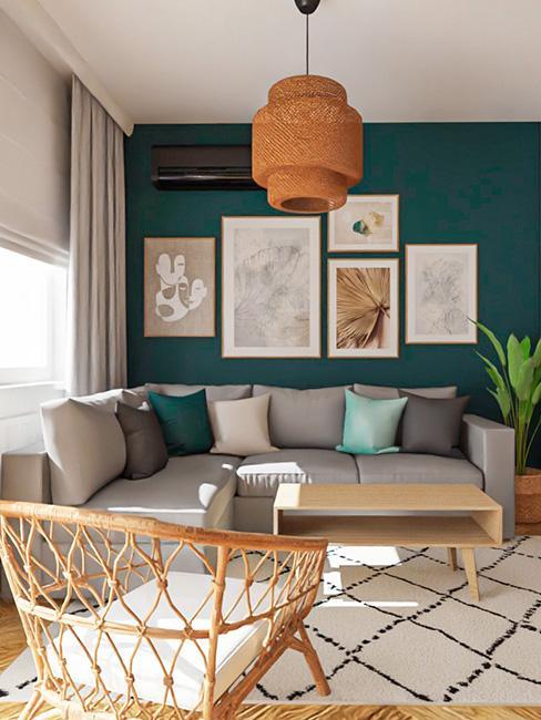 Mały salon na tle zielonej ściany z galerią grafik i szarą sofą
