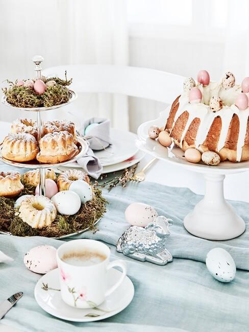 Zbliżenie na stół z błękitnym obrusem i dwoma paterami z słodkościami
