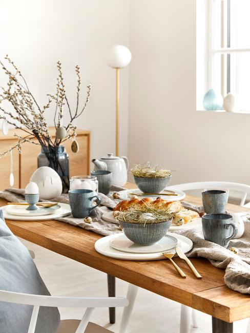 Drewniany stół w niebieską zastawą stołową w stylu skandynawskim oraz wazonem z dekoracją gałązek
