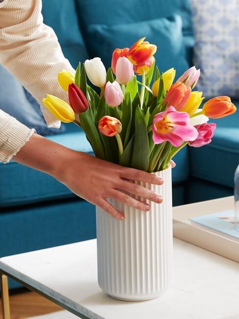 Biały wazon z tulipanami na stoliku kawowym