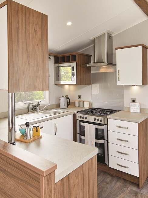 Drewniano-kremowe meble w kuchni U w małym mieszkaniu