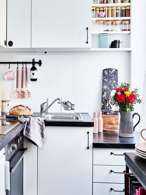 Biała kuchnia z ciemnym blatem i różnordnymi akcesoriami kuchennymi
