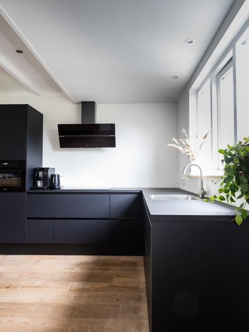kuchnia w kształcie litery L z czarnymi meblami i jasnobrązową posadzką