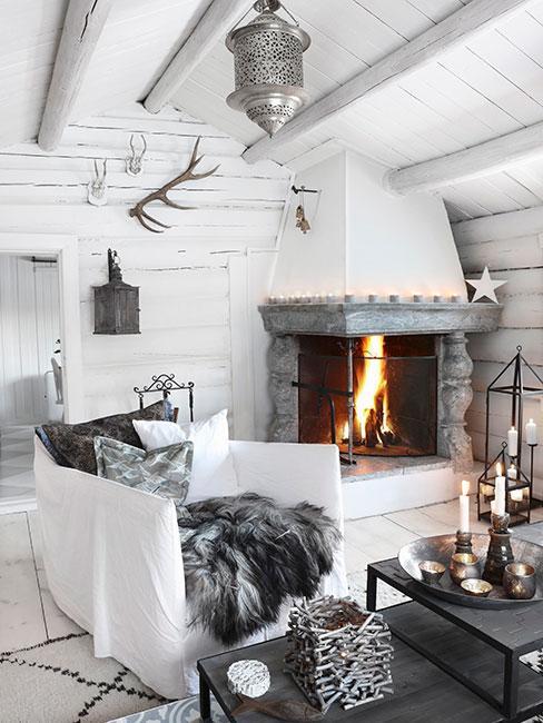 Biały salon w drewnianym domu z kominkiem i szarymi meblami