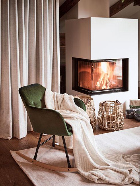 Przytulny kącik z zielonym fotel bujanym z aksamitu obok kominka