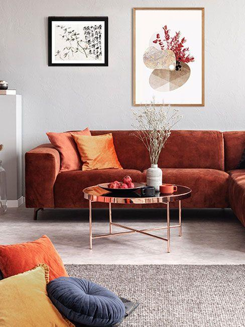 Ciepłe kolory w salonie - wyrazista ruda kanapa, pomarańczowe i żółte poduszki