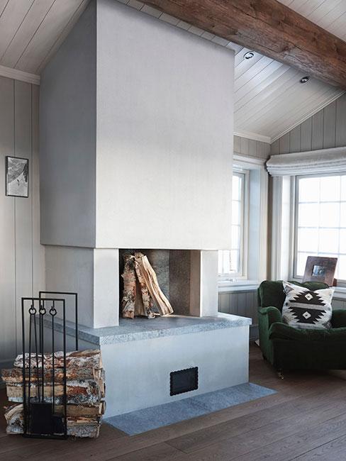 Biały kominek w przestronnym pokoju w stylu skandynawskim