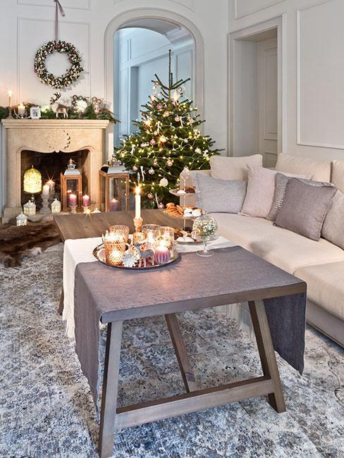 Duży salon w kamienicy z białą sofą, szarym drewnianym stołem i kominkiem w tle