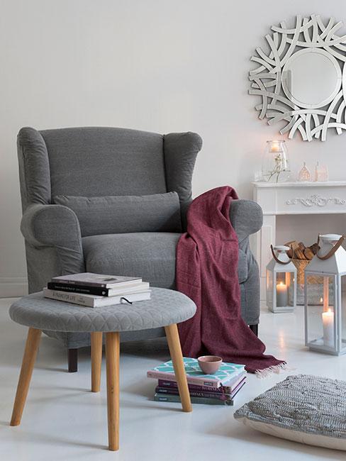 przytulny salon z dużym szarym fotelem uszakiem przy portalu kominkowym